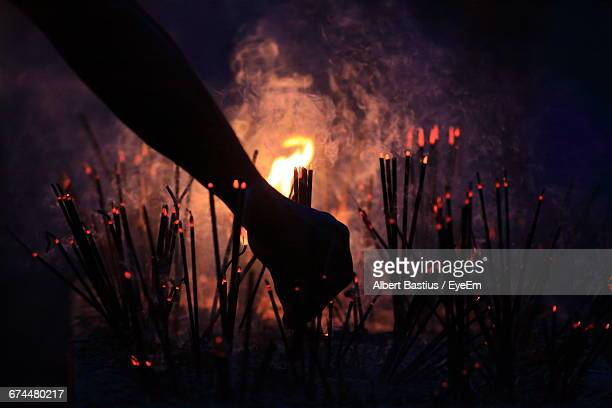 silhouette of hand amongst incense sticks - ceremony stock pictures, royalty-free photos & images