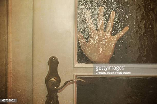 silhouette  of hand coming opening the door slowly - human trafficking stock photos and pictures