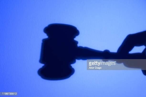 silhouette of hand with a judge's gavel. suspense of payments. - corruption stock pictures, royalty-free photos & images