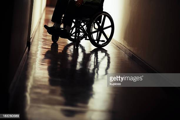 Silhouette of handicapped man sitting on wheelchair in hospital hallway