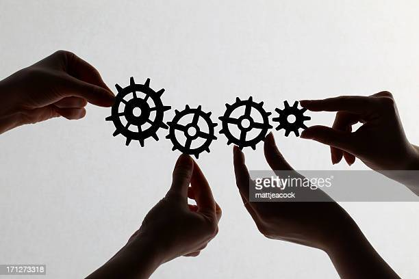 Silhouette of hands holding cogs and gears