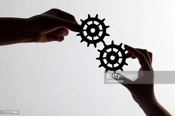 Silueta de manos sosteniendo cogs y engranajes