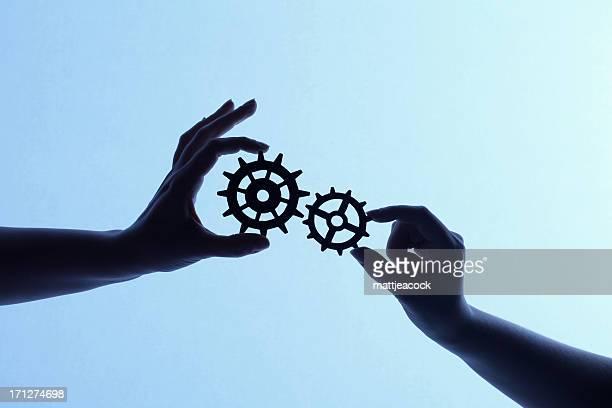 Silhouette der Hände holding Zahnräder und Getriebe