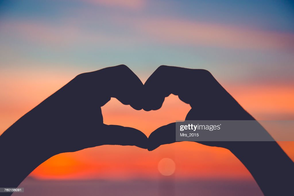 Silhouette of hands making a heart shape at sunset : Stock Photo