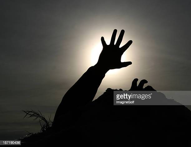 silhouette of hands reaching for a grip, blocking the sun