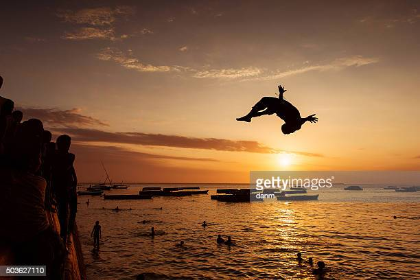 Silhouette of Happy Young boy jumping in water at sunset in Zanzibar