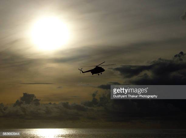 silhouette of helicopter over the ocean - indian air force stock-fotos und bilder