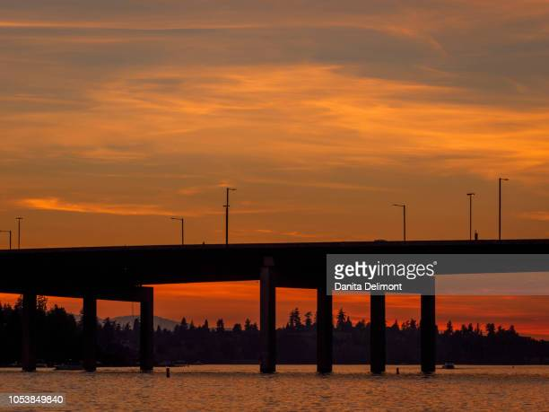 silhouette of highway bridge over lake washington at sunset, bellevue, king county, washington state, usa - bellevue washington state stock photos and pictures