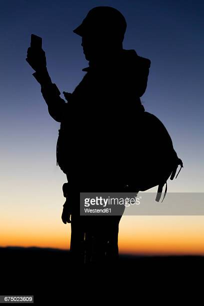 Silhouette of hiker looking at smart phone
