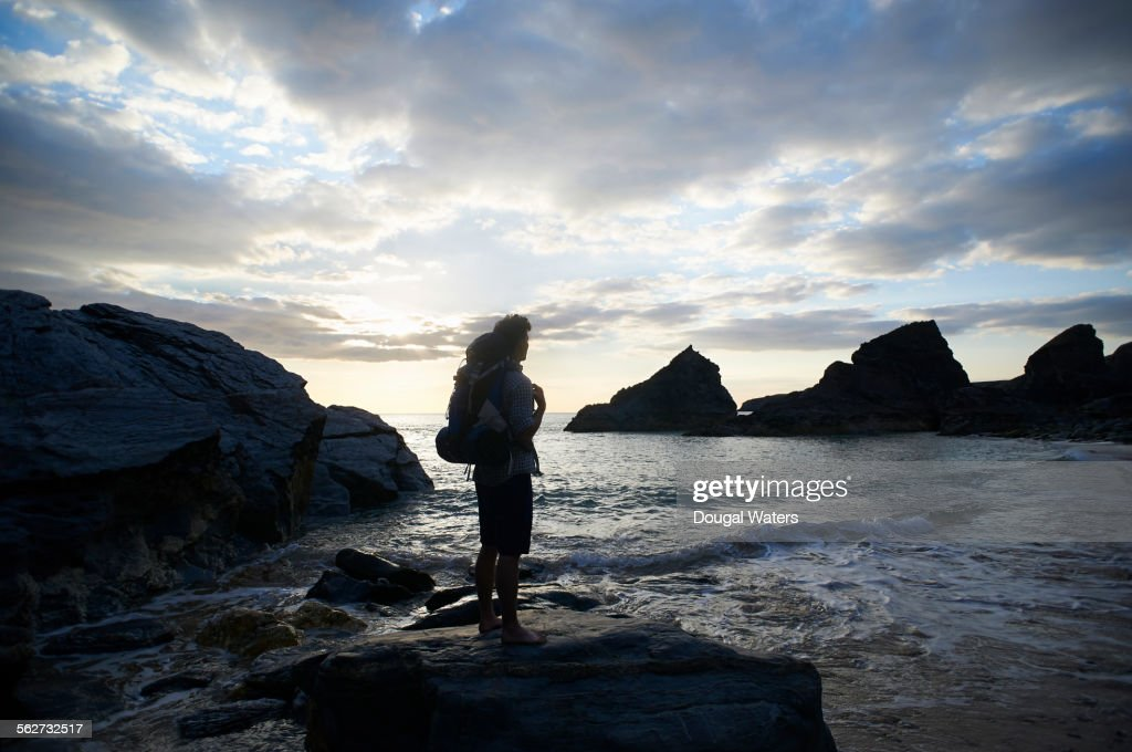Silhouette of hiker looking out to sea : Stock Photo
