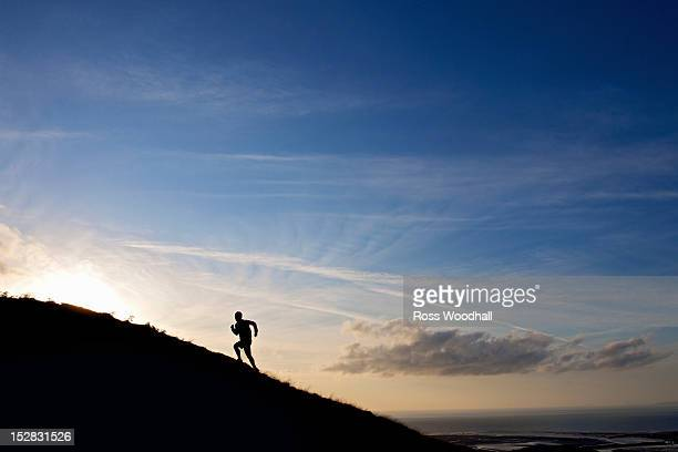 Silhouette of hiker running up hillside