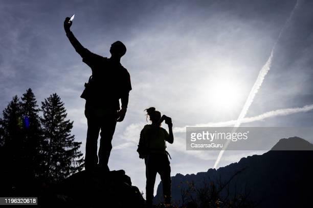 silhouette von wanderern fotografieren mit handys mit chemtrails am himmel - chemtrails stock-fotos und bilder