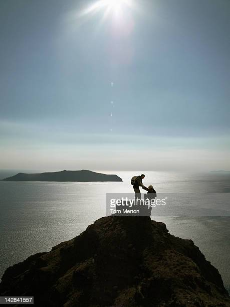 Silhouette of hikers scaling mountaintop
