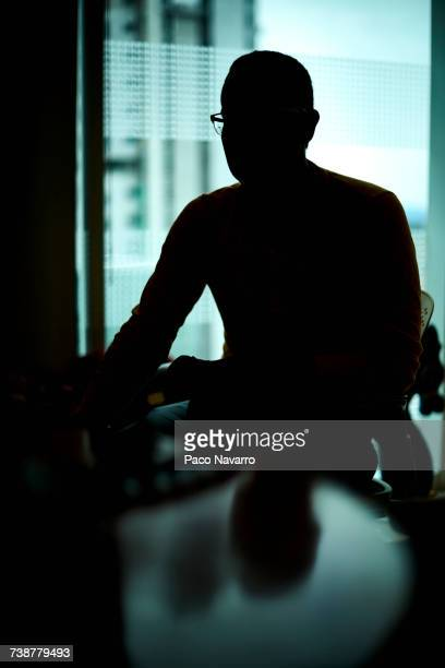 Silhouette of Hispanic man sitting at table