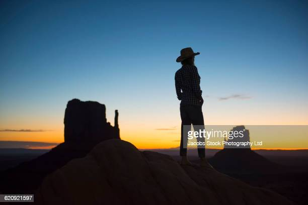 Silhouette of Hispanic woman and desert landscape at sunset
