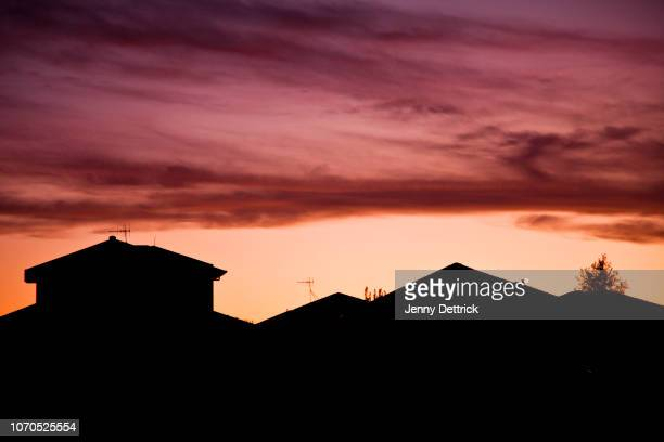silhouette of houses at sunset - suburban stock pictures, royalty-free photos & images