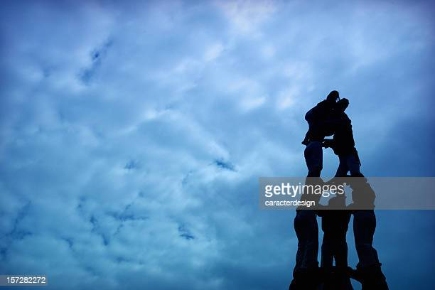 silhouette of human castle - castellers stock photos and pictures