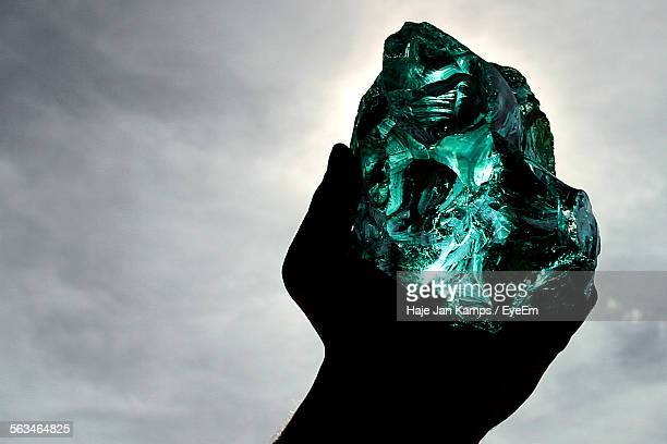 silhouette of human hand holding emerald crystal - emerald green stock pictures, royalty-free photos & images