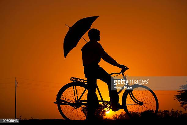 Silhouette of Indian man on bike at sunset