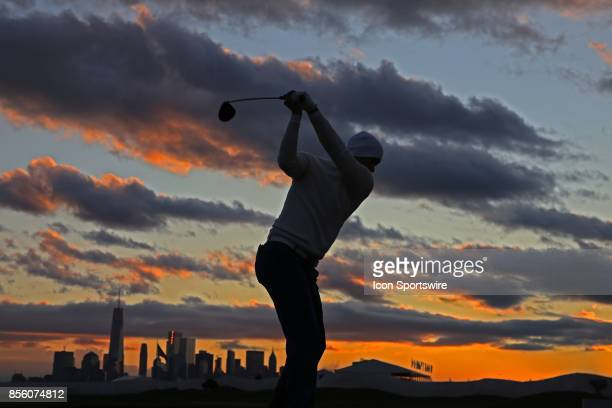 A silhouette of International golfer Adam Scott hitting golf balls at the practice range at sunrise with the New York city skyline in the background...