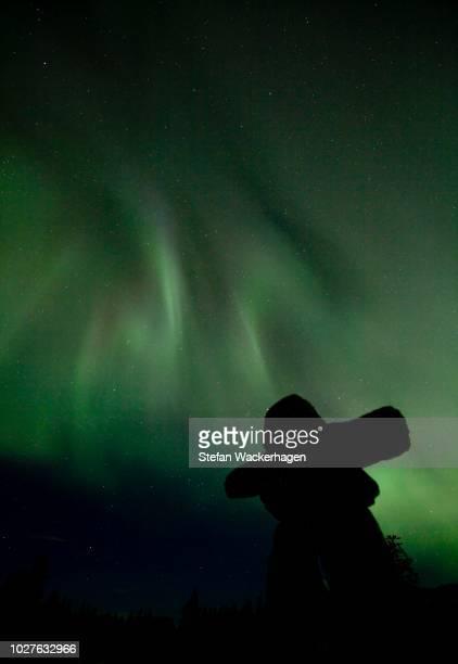 Silhouette of Inuit stone man, inukshuk, inuksuk, stone landmark or cairn, Northern or Polar Lights, Aurora Borealis, green, near Whitehorse, Yukon Territory, Canada