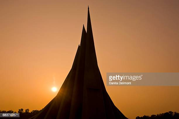 silhouette of jatiyo smriti soudho (national monument for martyrs of bangladesh) at sunset, savar, bangladesh - savar stock pictures, royalty-free photos & images
