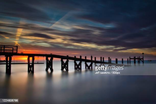 silhouette of jetty on sea, southend-on-sea, uk - southend on sea stock pictures, royalty-free photos & images