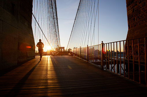 Silhouette of jogger on Brooklyn Bridge at sunset - gettyimageskorea