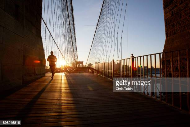Silhouette of jogger on Brooklyn Bridge at sunset