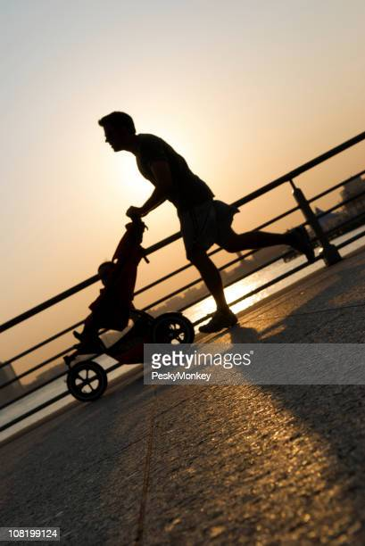 Silhouette of Jogging Father Pushing Stroller on Riverfront