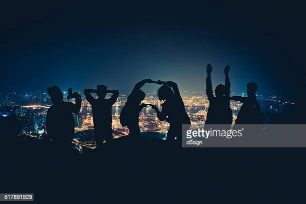 Silhouette of joyful hikers posing on mountain top