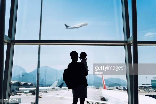 silhouette of joyful young asian father carrying cute little daughter looking at airplane through window at the airport while waiting for departure - emigration and immigration stock pictures, royalty-free photos & images
