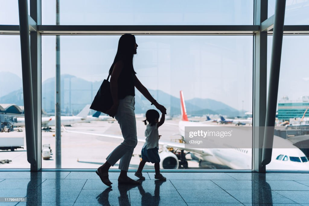 Silhouette of joyful young Asian mother holding hands of cute little daughter looking at airplane through window at the airport while waiting for departure : Stockfoto