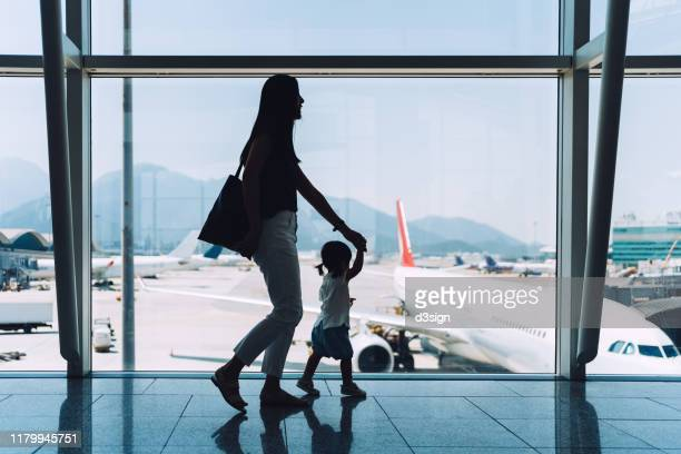 silhouette of joyful young asian mother holding hands of cute little daughter looking at airplane through window at the airport while waiting for departure - viaggio foto e immagini stock