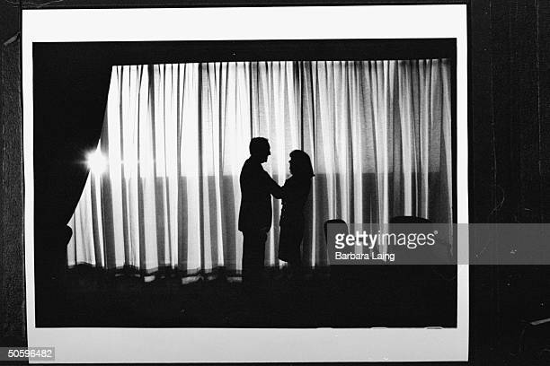 Silhouette of Kathleen Tobin Krueger fixing the tie of her husband TX Sen Bob Krueger as they stand in front of large white curtain at The Tower Club...