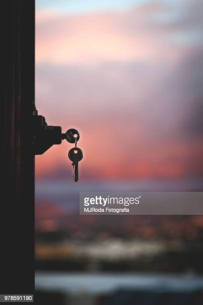 Silhouette of keys and door lock against cityscape, Malaga, Spain