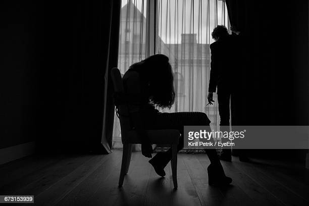silhouette of kidnapped woman and kidnapper - violenza foto e immagini stock