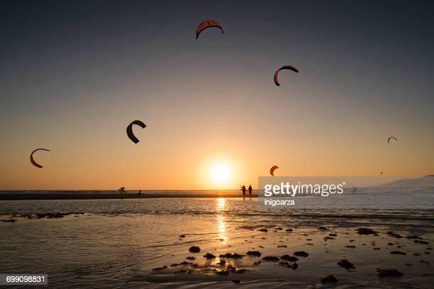 silhouette of kite surfers at sunset, los lances beach, tarifa, cadiz, andalucia, spain - tarifa stock photos and pictures