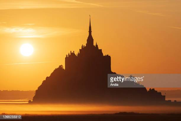 Silhouette of Le Mont Saint-Michel with an orangey light at sunrise .