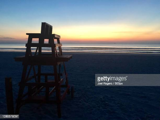 silhouette of lifeguard hut at beach against sky during sunset - joel rogers stock pictures, royalty-free photos & images