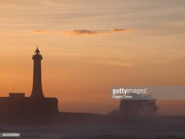Silhouette of lighthouse and a wave at sunset. Rabat, Morocco