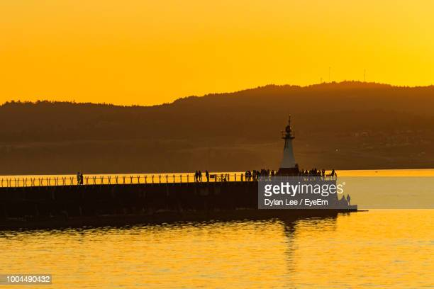 silhouette of lighthouse at seaside during sunset - vancouver island stock pictures, royalty-free photos & images