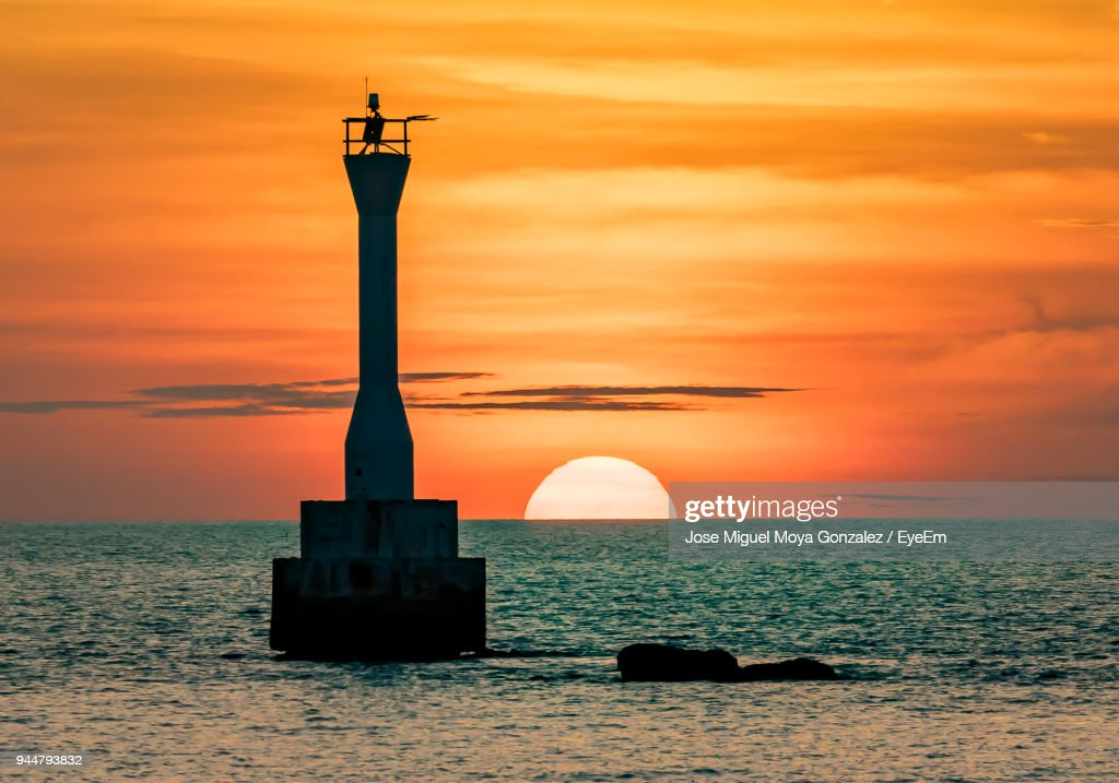 Silhouette Of Lighthouse At Sunset : Stock Photo