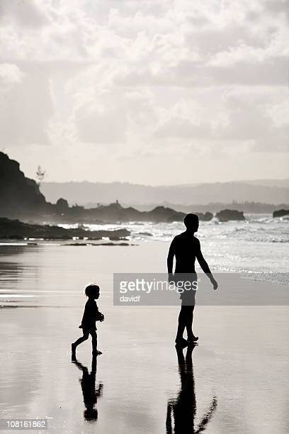 Silhouette of Little Boy Following His Father on Beach