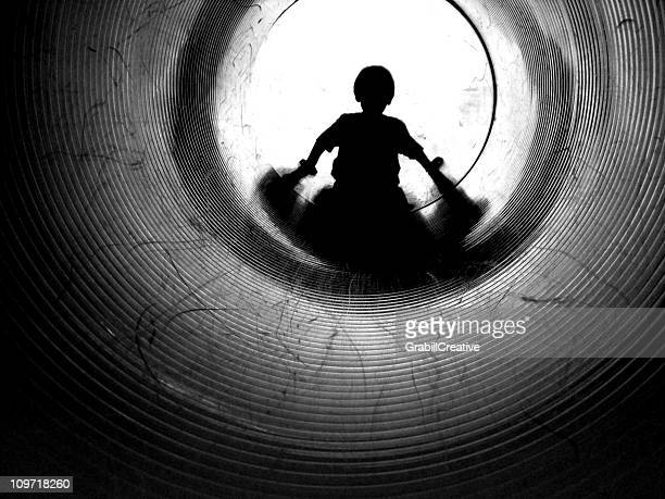 Silhouette of Little Boy Going Down Tunnel, Black and White