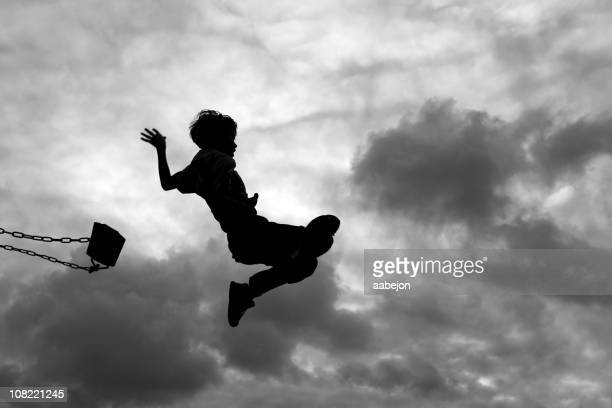 silhouette of little boy jumping off swing - swing stock pictures, royalty-free photos & images