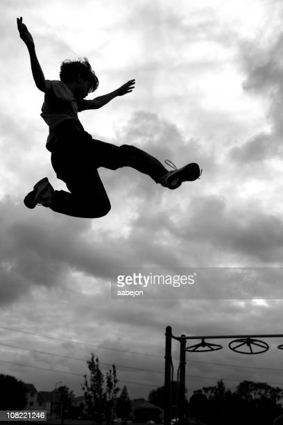 Silhouette of Little Boy Jumping with Playground in Background