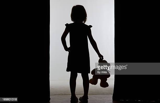 silhouette of little girl with teddy bear