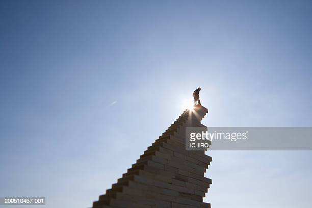 Silhouette of male figurine atop stairway, low angle view