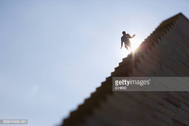 Silhouette of male figurine going up stairway, low angle view